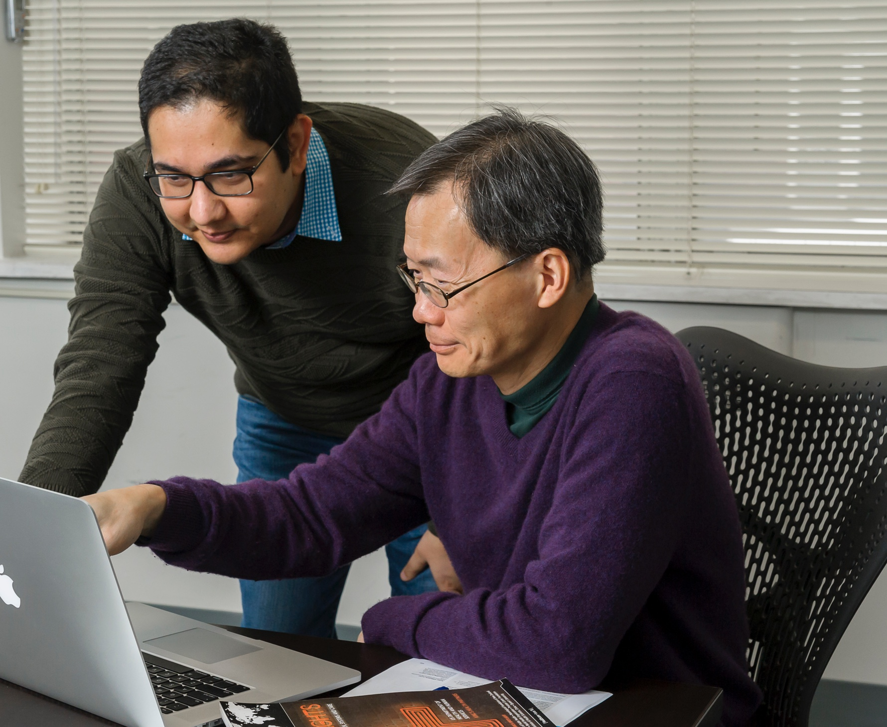 Scientists Drs. Hubert Wong and Ehsan Karim analyze data on computer, medical device clinical studies